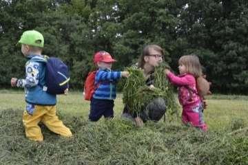 Děti s průvodkyní zkoumají, jak voní seno