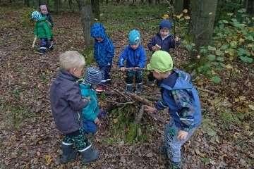Děti si v lese hrají s klacíky
