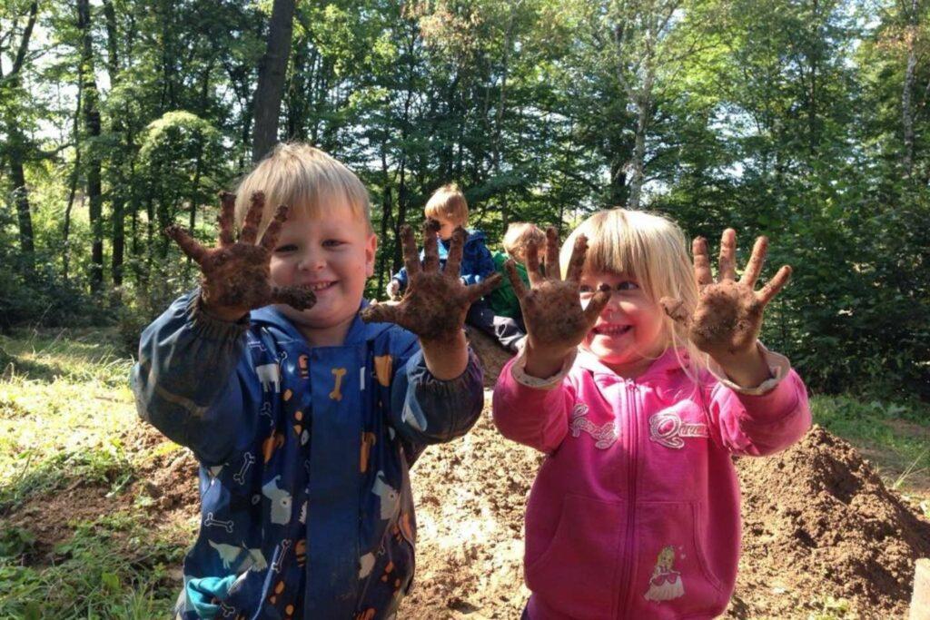 Kluk a holka se smějí svým rukám špinavým od bláta